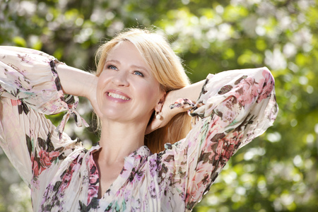 mid life: Happy mature woman in front of flowering tree in spring