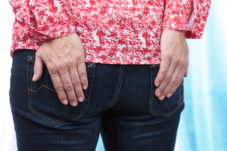 anus: Woman with pain in her anus holding the hands on her butt