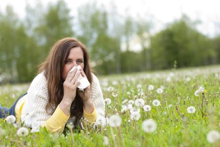 Ongelukkig van middelbare leeftijd vrouw met hooikoorts en zakdoek liggend in het gras