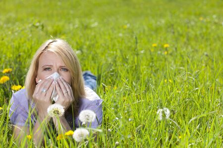 Mature woman with hayfever and handkerchief lying in the meadow Stockfoto