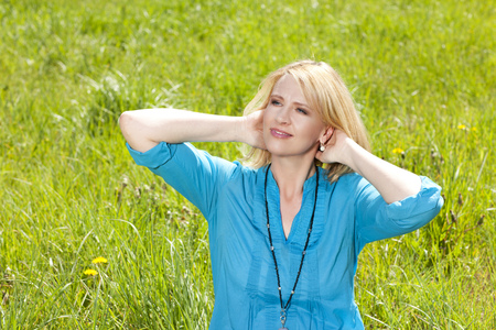 arms behind head: Happy mature woman in nature with arms behind her head sitting in the grass