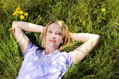 her: Happy matured woman lying in the grass on her back Stock Photo