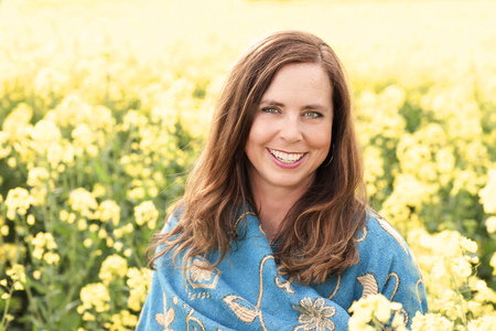 Happy middle age woman in yellow field in nature Imagens
