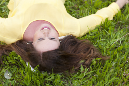 Happy middle age woman lying on her back in the grass in summer