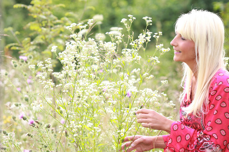 attractive middle age woman with natural flowers in summer Reklamní fotografie