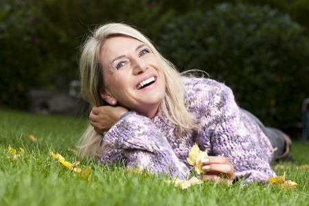 秋の草の笑顔で横になっている魅力的な成熟した女性