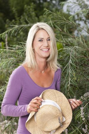 Happy woman with straw hat in her garden in summer Reklamní fotografie