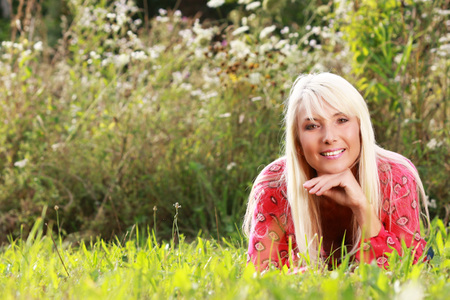 Attractive matured woman lying in the grass in summer