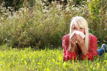 Matured woman lying in gras with handkerchief blowing her nose