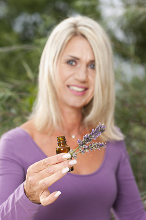 Happy matured woman with lavendar oil bottle  and lavender plants