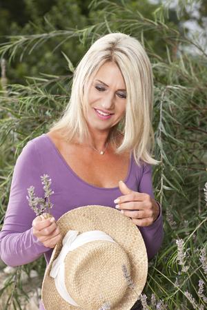 chapeau de paille: Heureuse femme avec chapeau de paille dans son jardin en été
