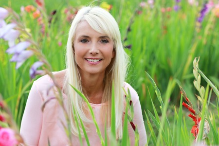 woman middle age: Attractive woman middle age in flower field