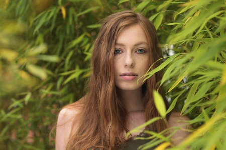 haired: Attractive red haired woman  outdoor with bamboo plants