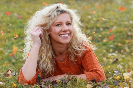 Matured woman enjoys leisure time in autumn outdoor lying in the grass