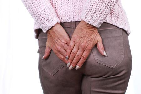 Frau mit Hämorrhoiden berührt ihre Knospe mit ihren Händen Standard-Bild - 72308138