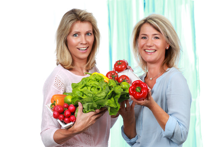 Two mature woman holding fresh vegetables Imagens