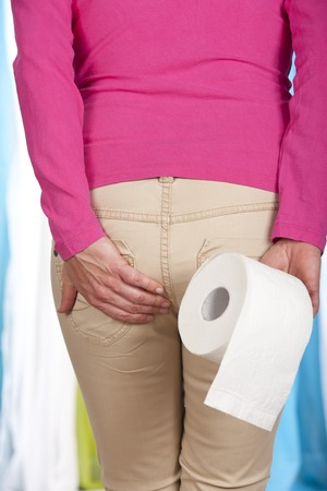 Woman with toilet roll behind her back