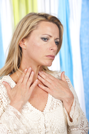Mature woman with hands at her throat with thyroid problems