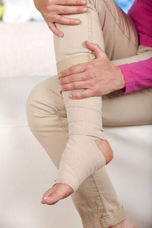 elongation: Bandage around a foot indoor Stock Photo