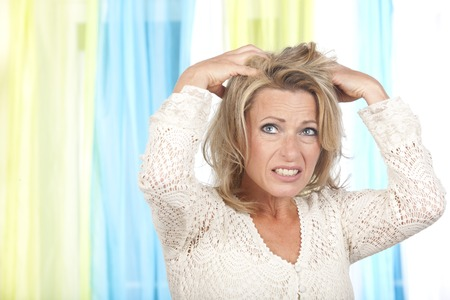 R: Mature woman with itchy and dry scalp Stock Photo
