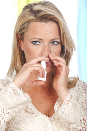 Woman with blocked nose applies nasal spray