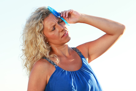Mature woman with ice pack in summer heat outdoor