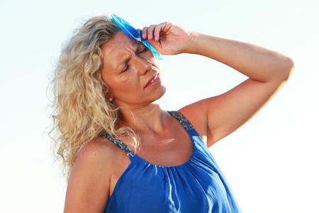 Rijpe vrouw met ijspak in de zomerhitte openlucht