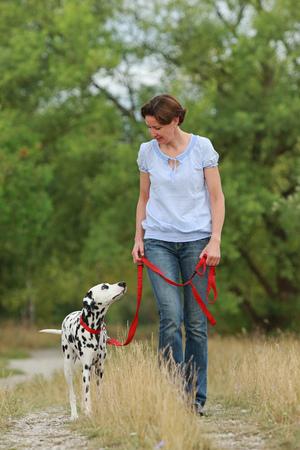 성숙한 여인 녹색 자연 환경에서 여름에 강아지와 함께 산책
