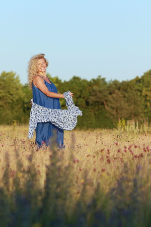 Happy mature woman is playing with a big shawl  in nature in summer