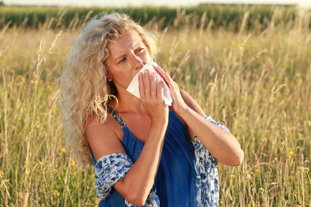 hankie: Mature woman with hayfever uses her handkerchief to blow her nose in  a meadow
