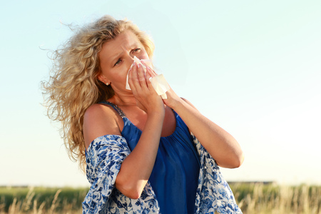 Mature woman with hayfever uses her handkerchief to blow her nose in  a meadow