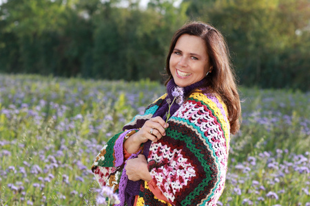 Happy mature woman with a big colorful scarf enjoys leisure in a lilac flower field Stock Photo