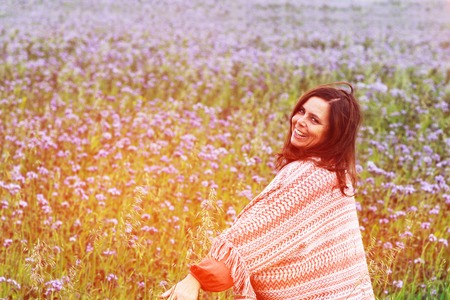 Happy mature woman with a big colorful scarf enjoys leisure in a lilac flower field Stok Fotoğraf