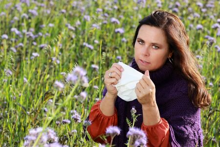 Mature woman with hayfever and allergy blows her nose with a handkerchief in a flower flied
