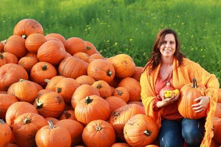 seasonable: Attractive mature woman holding big  orange pumpkin in front of a  collection of  freshly harvested pumpkins