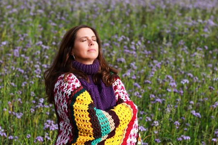 Happy mature woman enjoys the autumn sun in a flower field with eyes closed