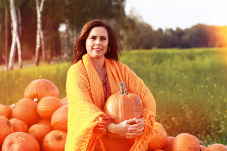 Attractive mature woman holding big  orange pumpkin in front of a  collection of  freshly harvested pumpkins