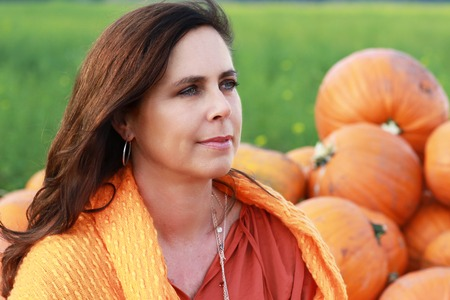 Attractive mature womans face  in front of a  collection of  freshly harvested pumpkins Stock Photo