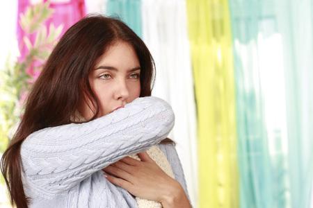 Vrouw hoest in de boef van haar arm