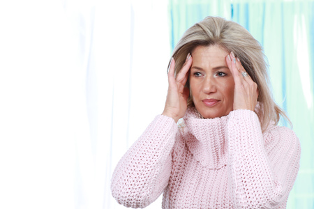 Mature woman touches her forehead with her hands, having headache