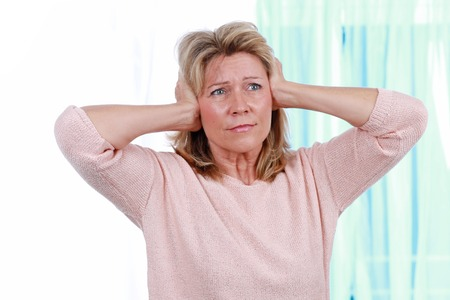 성숙한 여인은 귀에서 귀를 막기 위해 손을 매우 단단히 유지합니다.