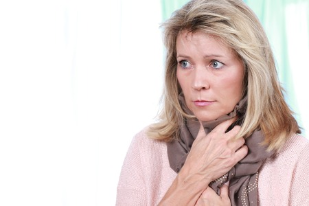 Mature woman keeping her throat warm with a scarf