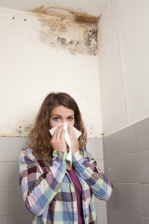 Woman with handkerchief in front of a mould spot