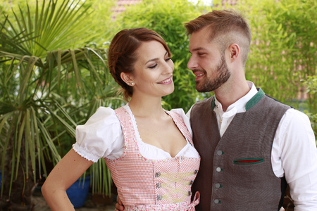 Happy bavarian couple looking at each other outdoor
