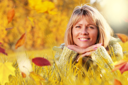Attractive mature woman lying relaxed in grass in golden Fall with autumn leaves Stock Photo