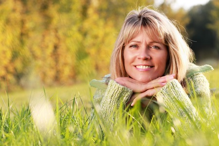 Attractive mature woman lying relaxed in grass in autumn