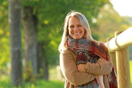 행복한 성숙한 여자가 가을 자연 산책 스톡 콘텐츠