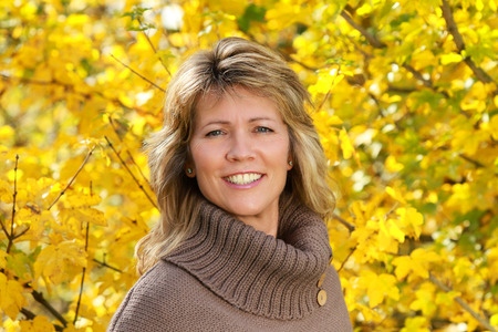 portait: portrait of an attractive happy mature woman in front of yellow autumn leaves outdoor