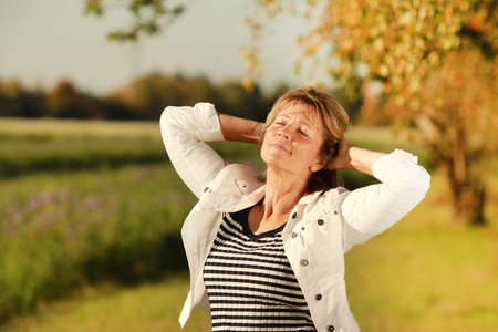 Happy mature woman enjoying the sun with eyes closed and hands folded in her neck