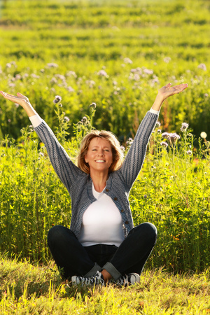Happy middle aged woman stretching her arms out while sitting in the meadow Zdjęcie Seryjne